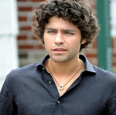 Guy with curls and an unbuttoned shirt