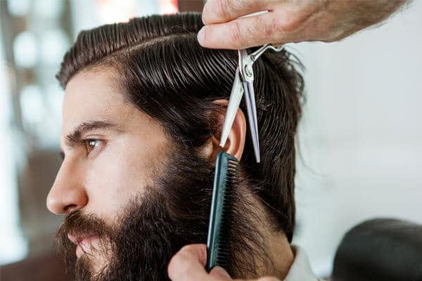 bearded man getting a trim