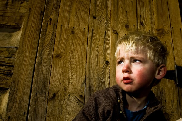 boy standing against a wooden wall