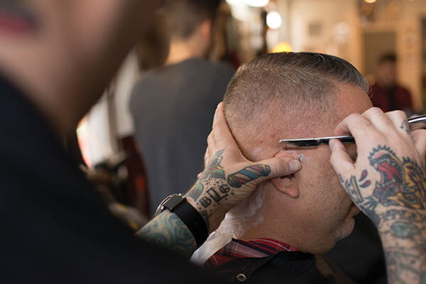 hairstylist with tattoo using a razor
