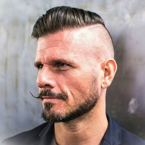 man smiling with moustache and a high an tight haircut