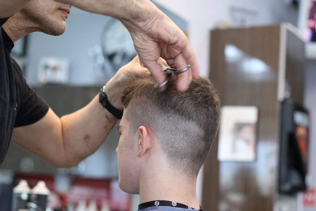 barber doing a haircut to a teen boy