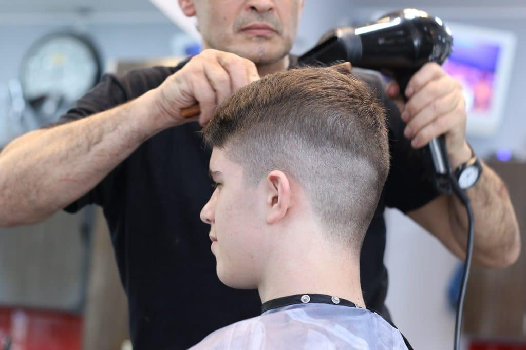 a boy getting a crew cut in barbershop