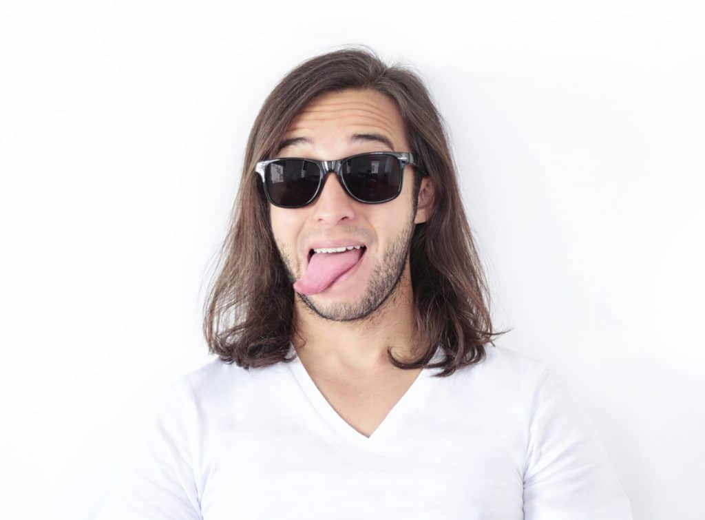 man wearing shades posing with his tongue out