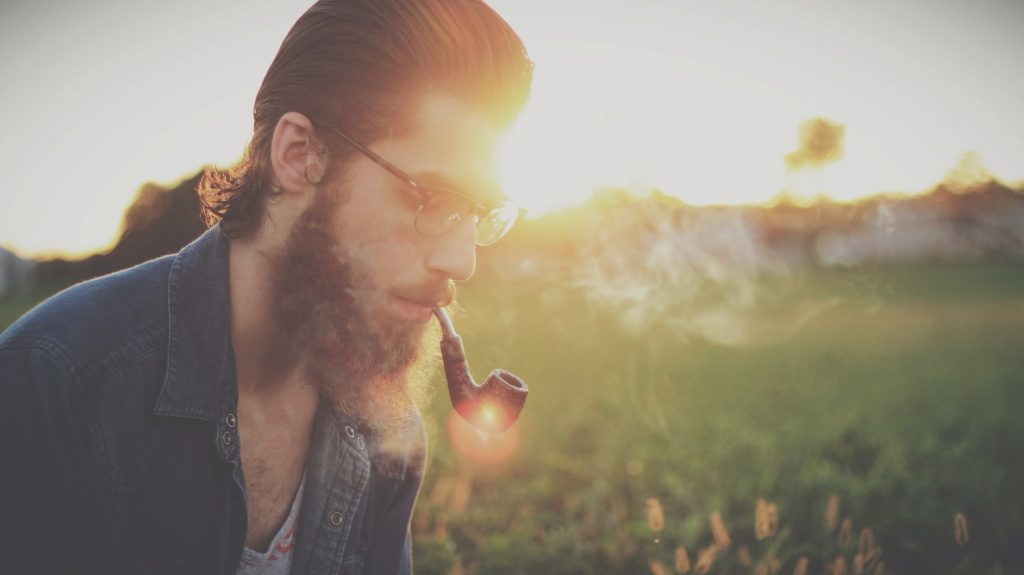 man with glasses smoking in an open area