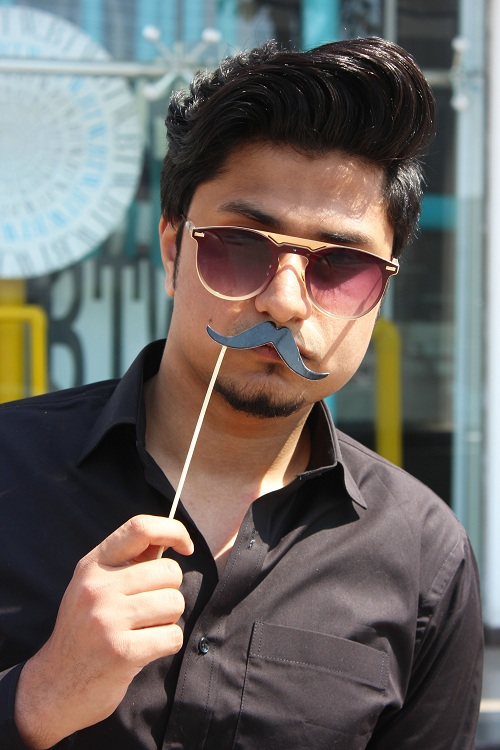 Man with a cool modern pomp hairstyle is holding a mustache stick and put it to his upper lip