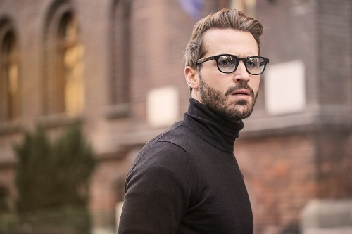 Man with a swooper hairstyle is wearing a black sweater and a eyeglasses