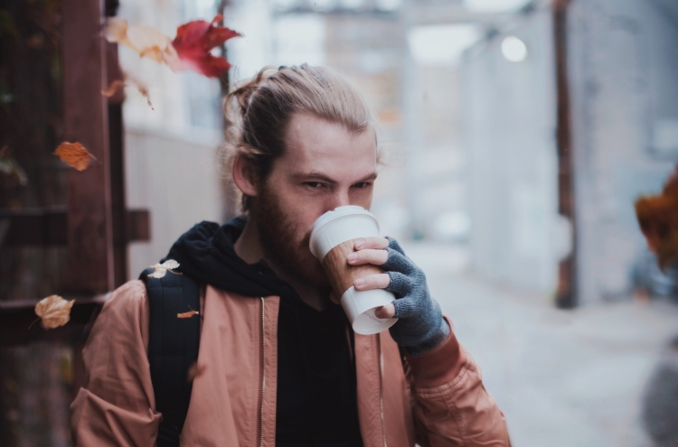 man drinking coffee autumn leaf falling featured image fall hairstyles